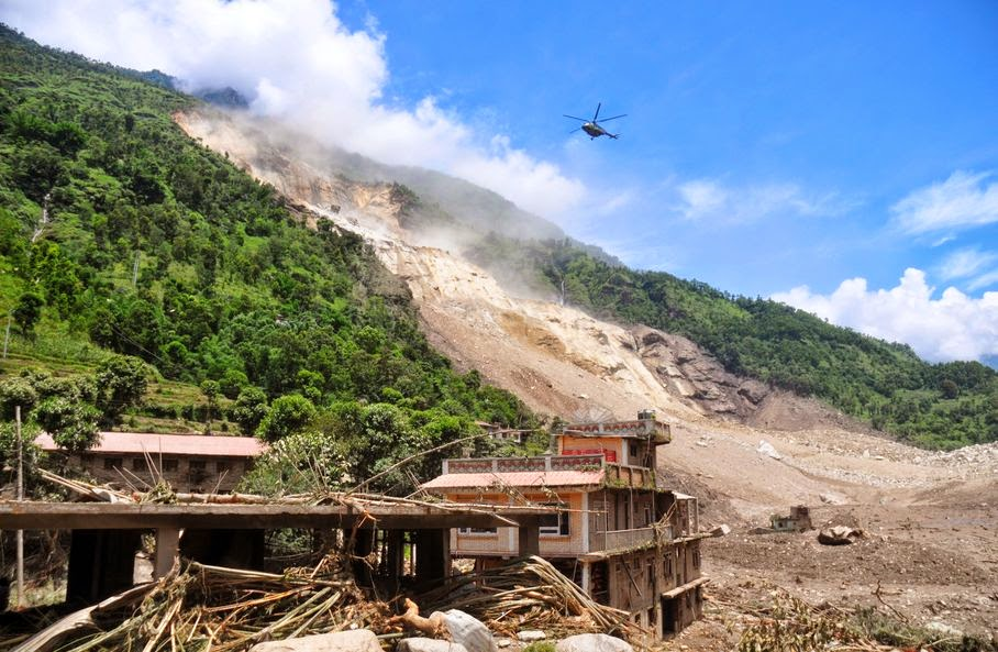 A Nepalese Army helicopter flies over the site of a landslide during a rescue operation in Sindhupalchowk area, about 120 kilometers (75 miles) east of Katmandu, Nepal, Saturday, Aug. 2, 2014. A massive landslide killed at least eight people and blocked a mountain river in northern Nepal on Saturday, causing the water to form a lake that was threatening to burst and sweep several villages, officials said.