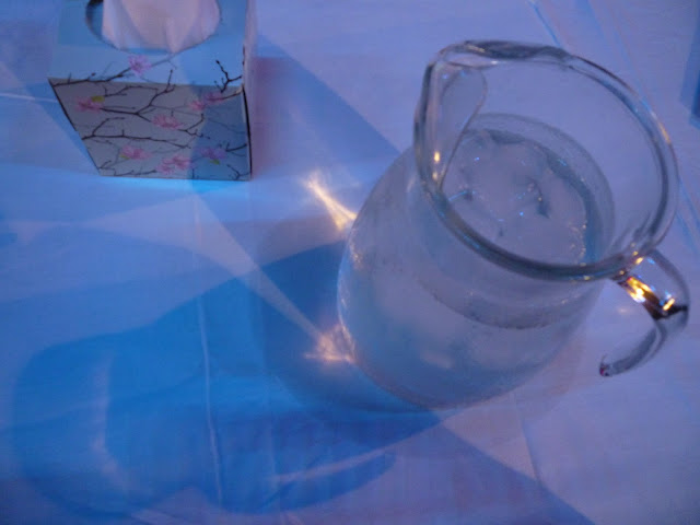 A jug of water on a white table cloth and a box of tissues