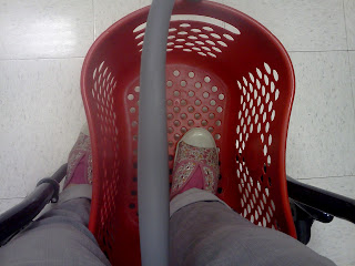 a picture of my feet while using my wheelchair, Target shopping basket propped on the footplate, one foot in the basket