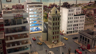 model city with office buildings, cars, people, as part of a model railroad exhibit