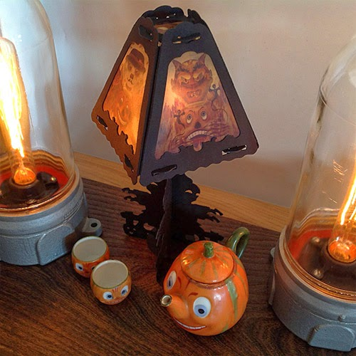 Table setting with antique lights and tea set featuring vintage-style Halloween lanterns design (devil and scarecrow) by Bindlegrim