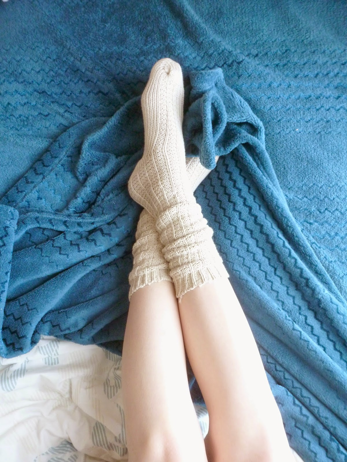 Shot of legs with cosy socks and fluffy blue blanket on a bed