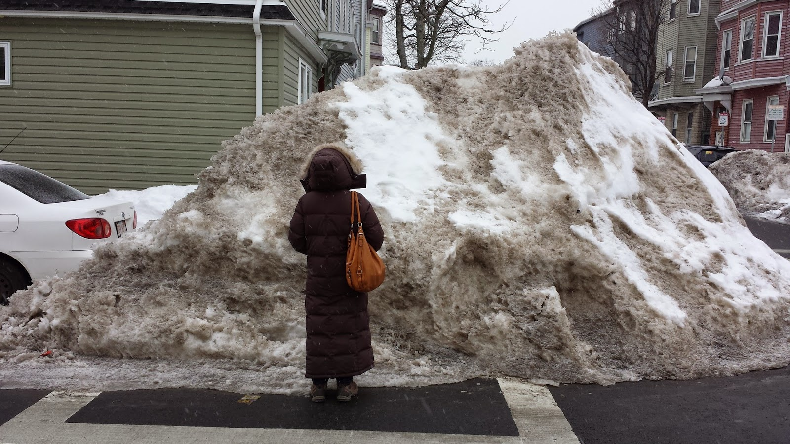 pedestrian standing in front of snow pile