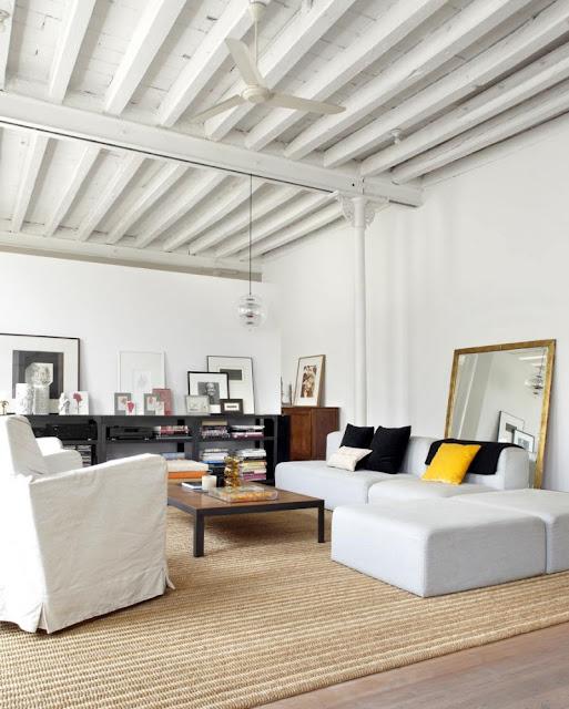 salon en loft con decoracion blanca, moderna y vintage con sofas de ikea blancos y combinacion de cuadros sobre mueble