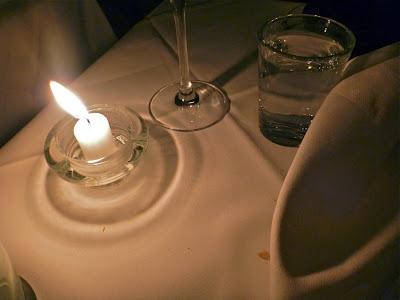 Kerze, Gläser, Stoffserviette, Krümel auf Stofftischdecke