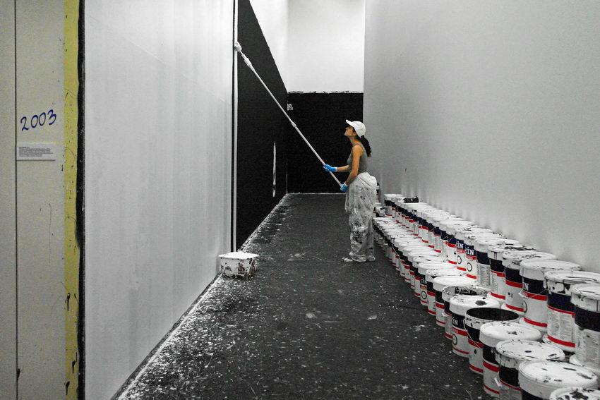 Corredor preto com uma mulher a pintá-lo de branco. Sobre o lado direito, dezenas de latas de tinta branca e preta, de 25 litros. À esquerda, um pequena placa com a explicação desta performance