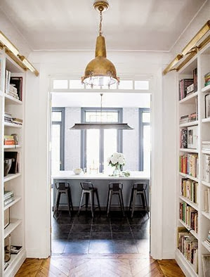 View into a NYC kitchen from a hallway with built in bookshelves, herringbone wood floors and a brass pendant light