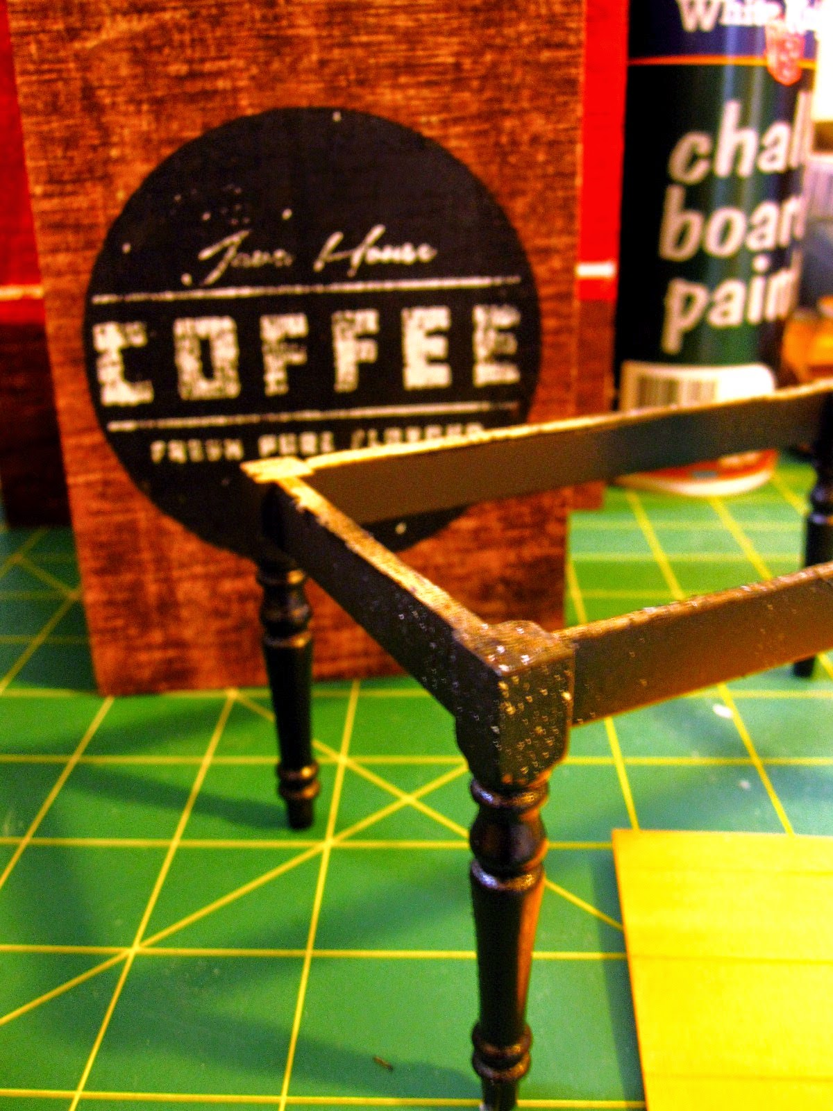 Miniature dining table leg assembly, painted black, sitting on a cutting mat with a spray can of chalkboard paint and a wooden coffee storage box.