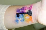 Key and colorful ink tattoo on wrist