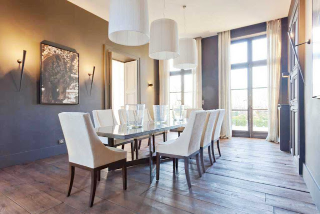 dining room with three pendant lights, torch lamps, two toned walls (gold and brown), wood floors, french doors with floor length curtains, a long table with white chairs