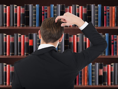 Man looking at law books on a shelf while scratching his head in confustion