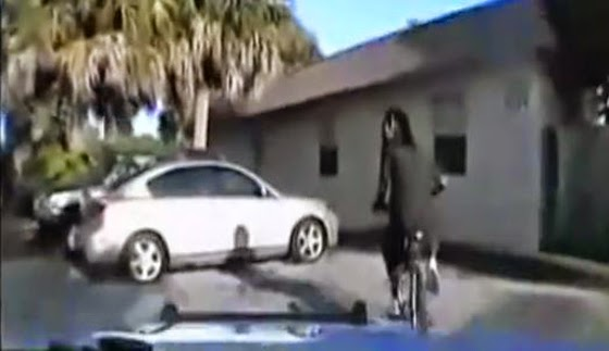 The victim was riding his bike when he noticed he was being followed by police.  So he got off his bike and  approached the police to see what they wanted - Police opened fire on him without warning and later lied about  what happened. (Screen capture from YouTube video).