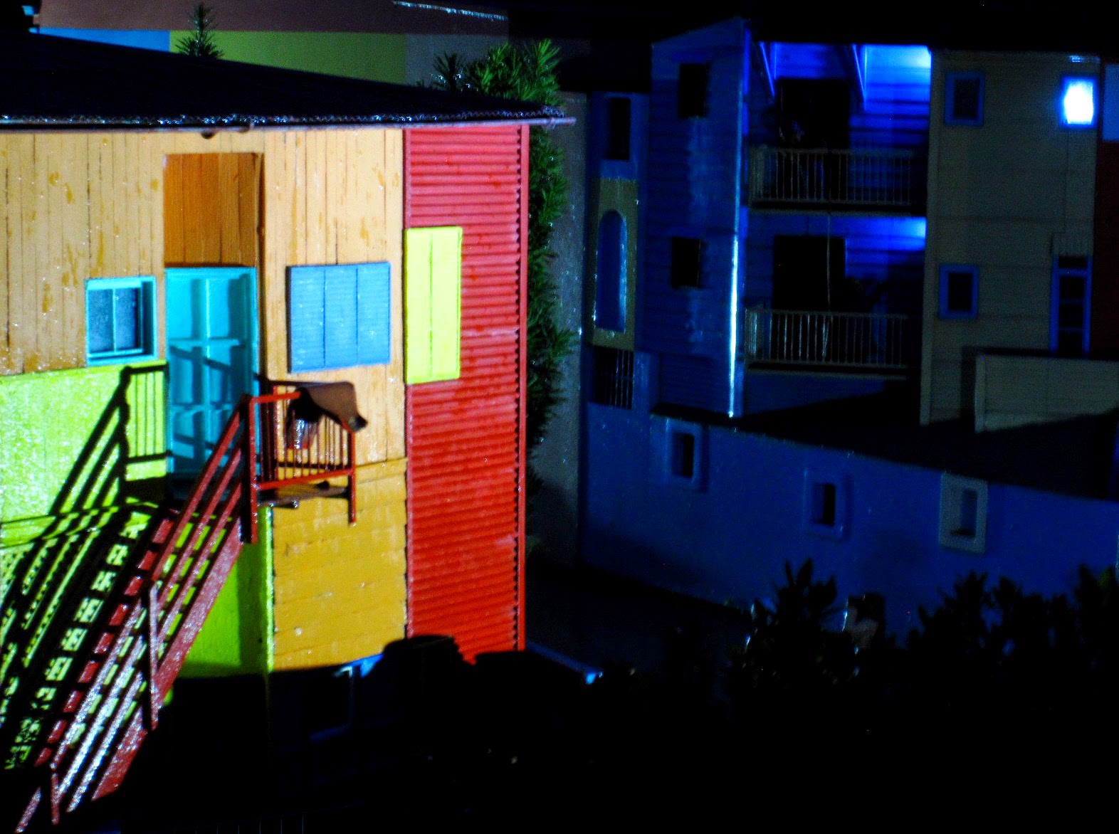 Miniature model of colourfull apartment buildings at night.