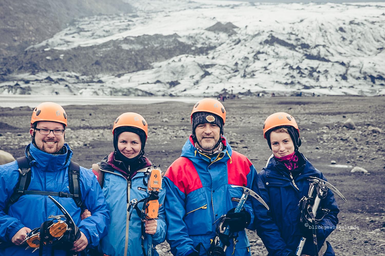 Vier bescheuert aussehende Touristen mit Helmen und Steigeisen und Pickel