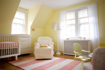 In this nursery the lemon yellow looks soft against the all white furniture  and window treatments.