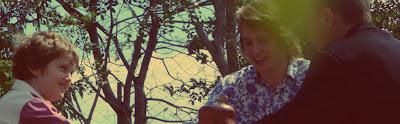 Foto: Gira-Giras do tempo -  colorida, três atores loiros e sorridentes sentados no chão. Eles interpretam, respectivamente,  o personagem Raul criança, na adolescência e fase adulta. Não é possível ver o rosto do adulto devido à luminosidade da foto. A foto é tirada de baixo para cima e ao fundo aparece os galhos de uma grande árvore.