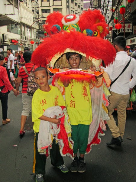 CHINATOWN: Boys play the dragon dance along the street