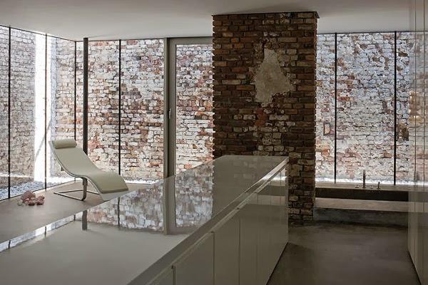 Ściany z okien i cegieł, białe meble lakierowane na wysoki połysk