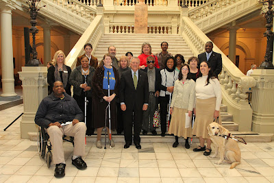 Yellow Lab Guide Dog Lassen, his handler Betsy Grenevitch, and the Georgia Statewide Coalition on Blindness group, with Governor Nathan Deal on the capitol building steps