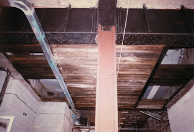 Looking up from the middle of Lower Queen's tunnel to steel girders and what appears to be a wooden floor.