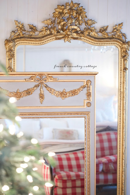 Gold and french blue mirrors stacked on floor reflecting a Christmas tree.