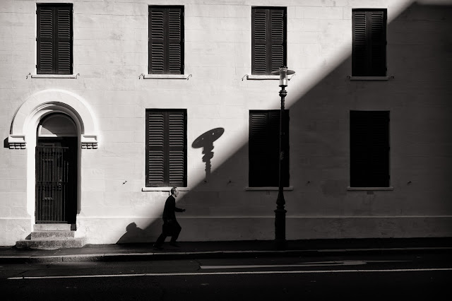 A man runs holding his briefcase in this street photograph from Cape Town South Africa