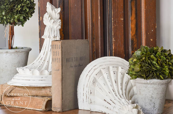 Using architectural salvage pieces like old corbels or worn doors enhances a display and gives it a little old world charm.  |  www.andersonandgrant.com