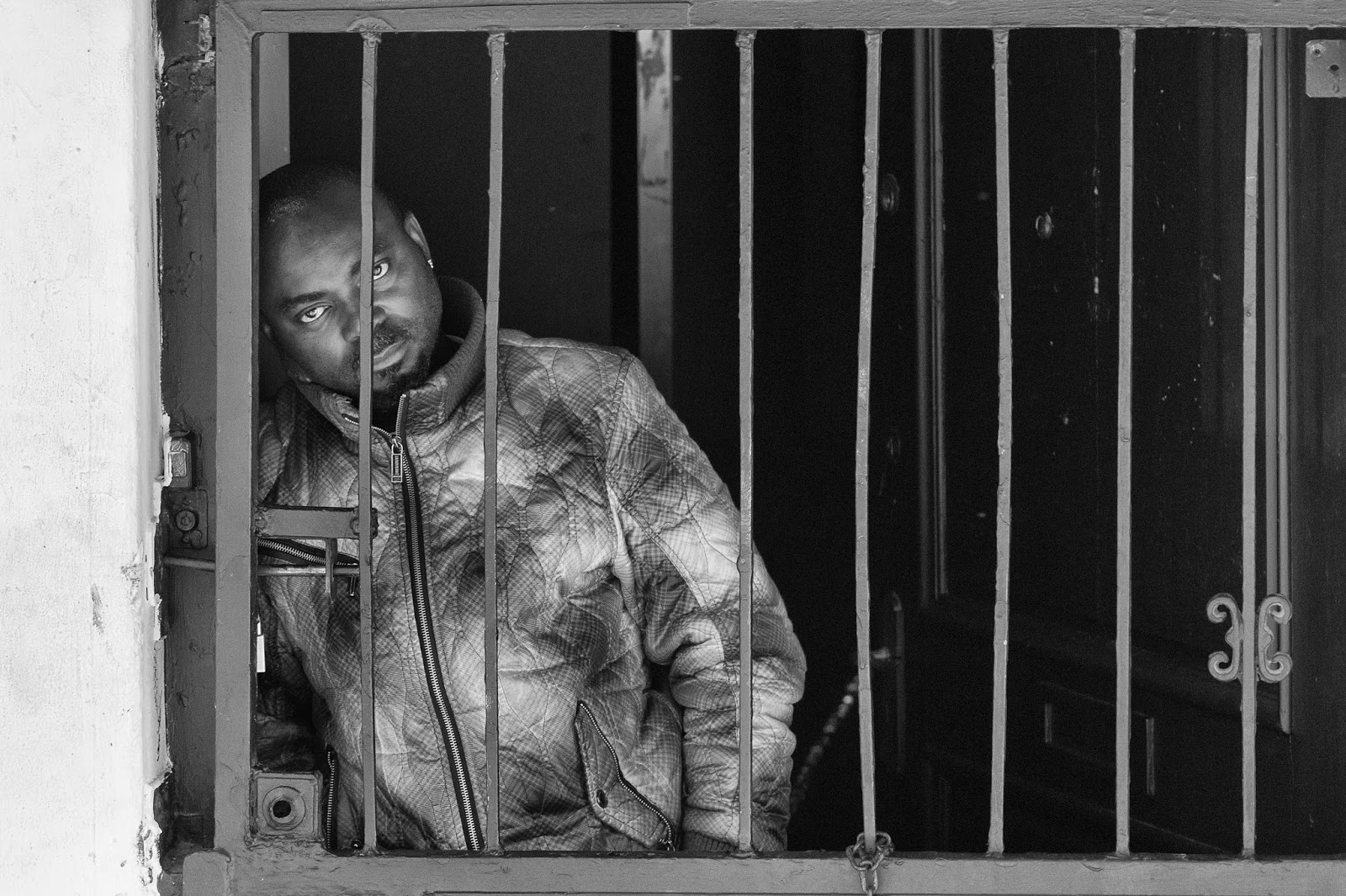 A man leans against a wall behind the bent bars of a security gate.