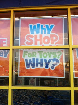 Colorful sign in a store window that appears to read Why shop for toys? Why?