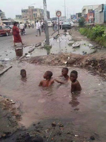 Photo of children bathing inside a large water-filled pothole