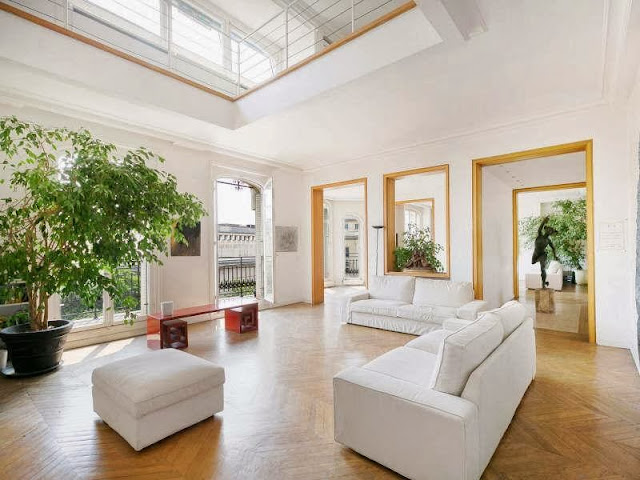 Living room in a Paris apartment with herringbone wood floor, white sofas and matching ottoman and a large potted plant