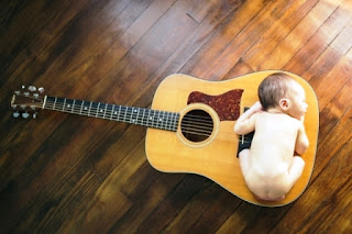 Gambar bayi lucu imut tidur di atas gitar