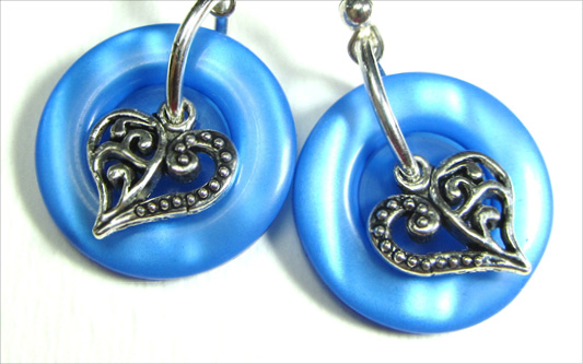 Drop dangle earrings have silver heart charms layered over shiny blue buttons