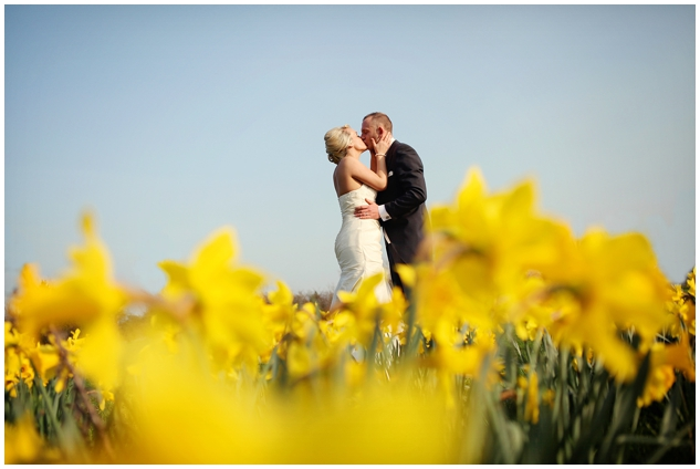 Bride and groom standing in field of yellow daffodils for their London wedding