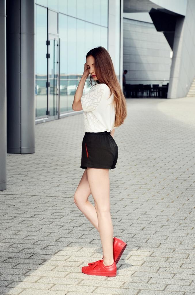 fit kobieta z długimi włosami oraz trampkami adidas superstar