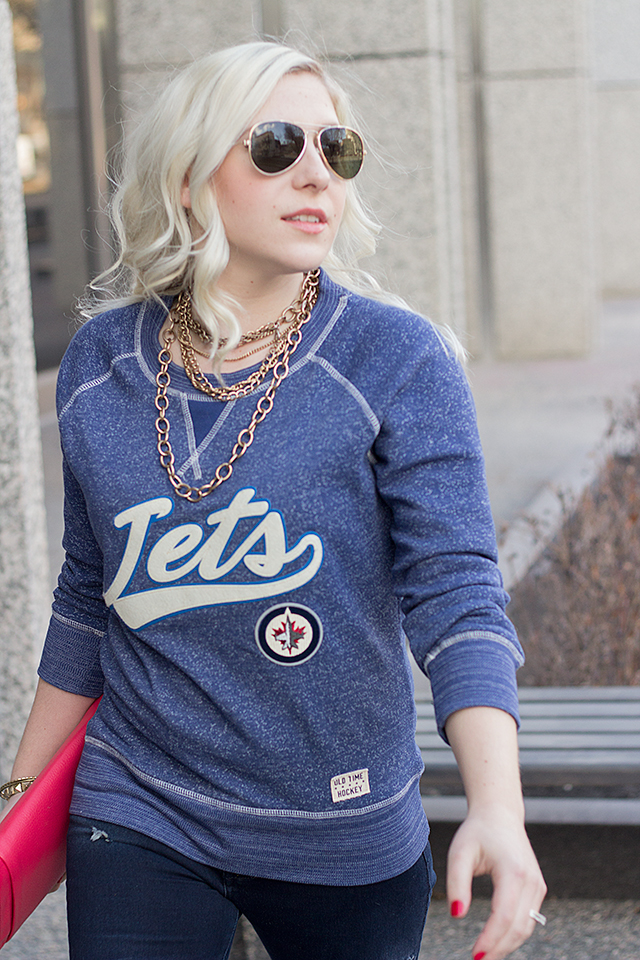 Jennifer Ashley wearing a Jets sweater, gold accessories and aviators.