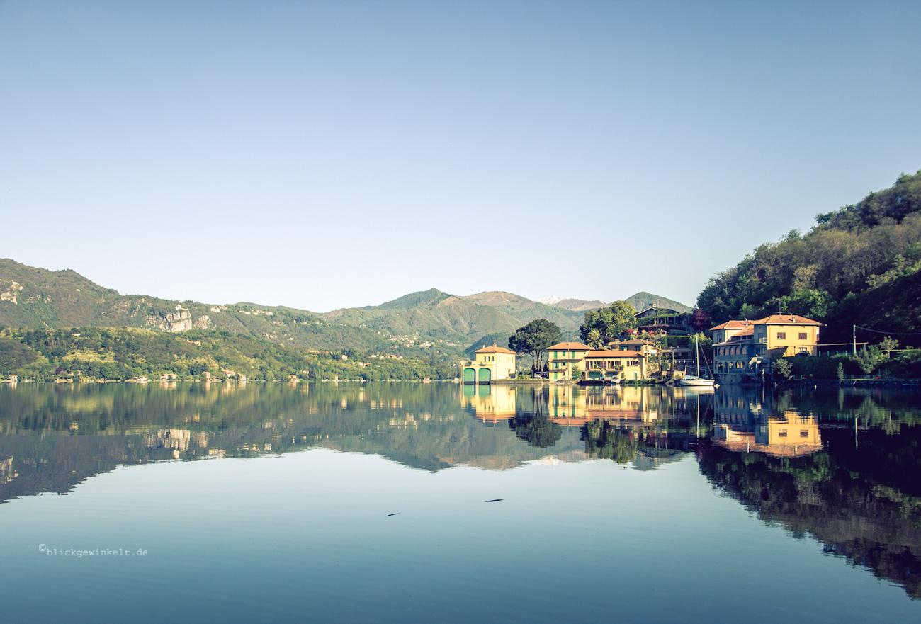 Häuser spiegeln sich im See im Morgenlicht