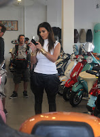 Kim Kardashian typing a message on her phone at a Motorcycle Store