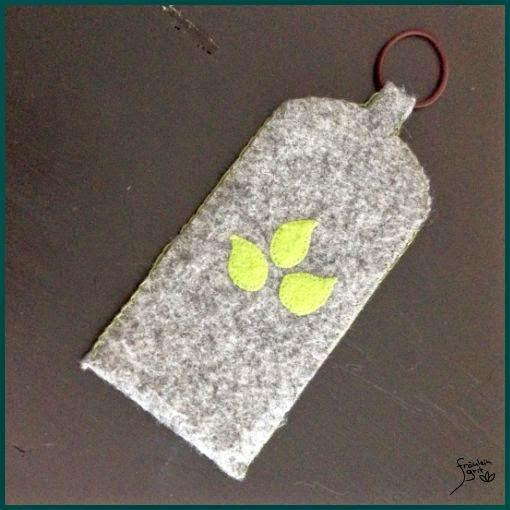 graue Handyhülle aus Filz mit grünen Blättern
