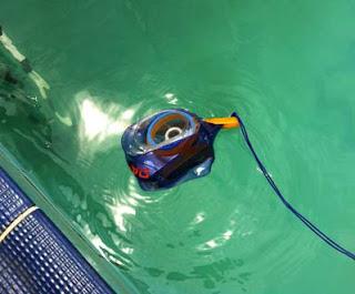 Foto da câmera boiando na beira da água da piscina.