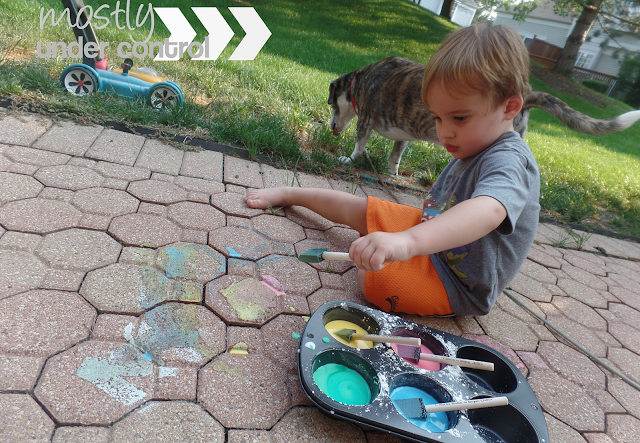 child painting with diy chalk paint with dog in the background