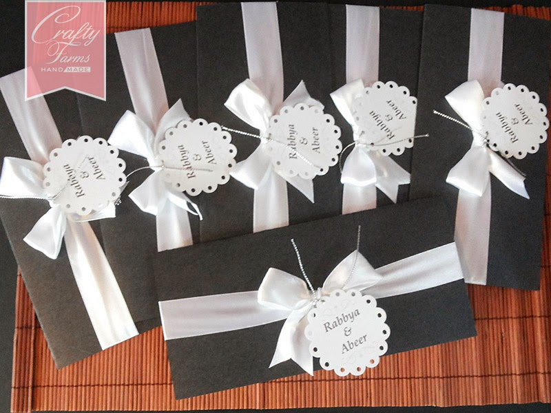 black and white wedding invitation cards are simply elegant and classic for a western wedding theme with a shimmery black base card with white satin ribbon
