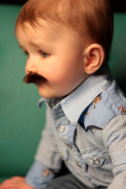 A really cute little boy with a mustache and a western shirt.