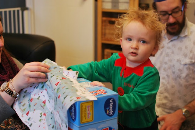 picture of toddler opening present with fuzzy hair