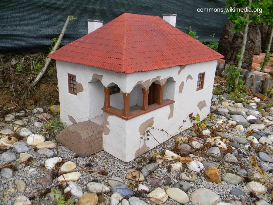 Casa miniatura de jardín hecha de concreto