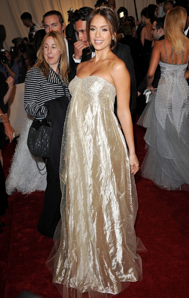 A pregnant Jessica Alba in a strapless glittering champagne-hued Ralph Lauren gown at the Met Gala