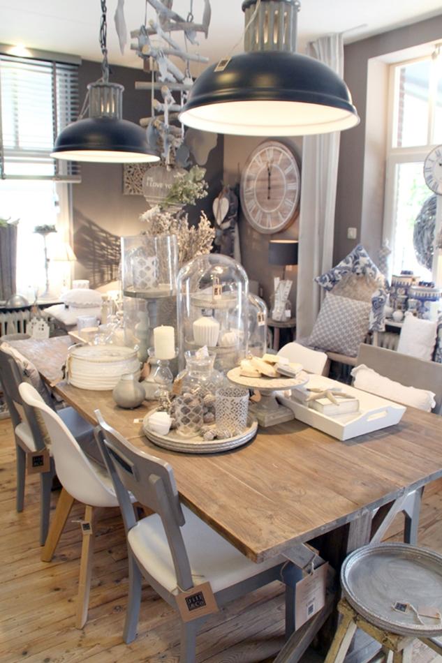 Dekorierter Tisch in beige schwarz mit Tellern Tablett und Kerzen darüber hängen zwei schwarze große Lampen im Industrialstyle