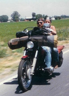 Couple riding a Harley Knucklehead chopper with a homemade bedroll
