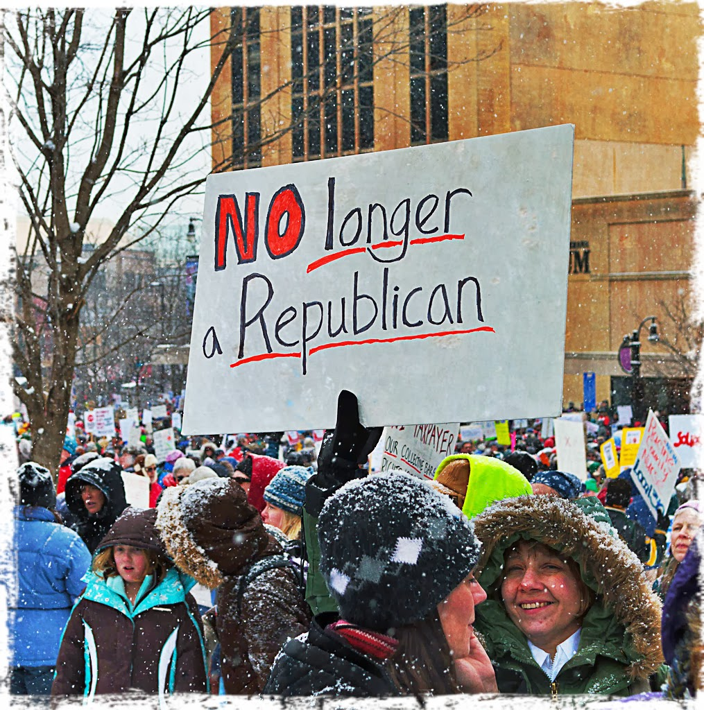Protester holds sign reading, 'NO LONGER REPUBLICAN'