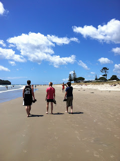 A shot of three boys, taken from the back, walking down a beach.